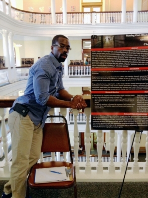 Anthony Powell stands with his poster presentation.