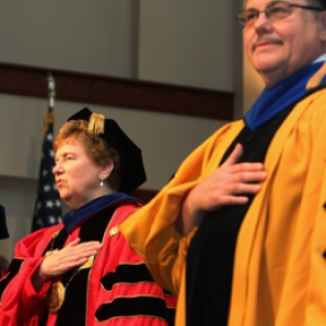 Sister Carol Jean Vale, SSJ, Ph.D., and Wolfgang Natter, Ph.D., vice president and dean of the faculty, salute the flag at the opening of Fall Convocation ceremonies.