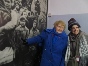 Eva Kor, standing with Marie Conn, Ph.D., points to a picture of herself as a young girl in Auschwitz.