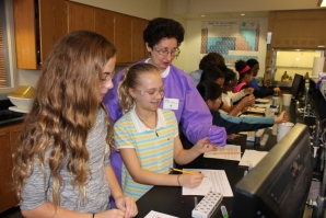 Janet Younathan, Ph.D., a scientist from J&J, works with two girls on the first part of the rainbow density lab.