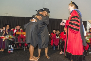 Mom and daughter hug on stage at Commencement