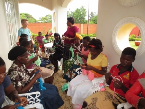 Sister Kathryn visits with former First Lady of Malawi, Madam Callista Mutharika, as she teaches young girls to knit.
