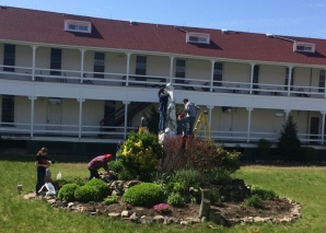 CHC volunteers work to clean the statue of St. Mary.