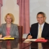 Jodie King Smith, vice president of enrollment management, and Michael Gomez, principal of Cristo Rey Philadelphia, sign the partnership agreement.